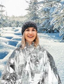Overly happy woman in emergency blanket